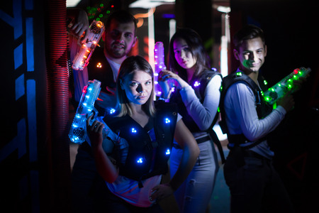 Group portrait of young people with laser guns having fun on dark lasertag arena