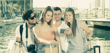 Four happy travellers making selfie with mobile phone on vacations 스톡 콘텐츠