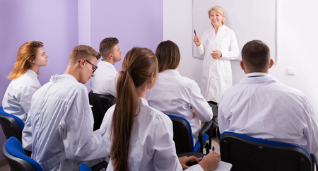 Elegant adult female teacher lecturing to medical students at auditorium Stok Fotoğraf