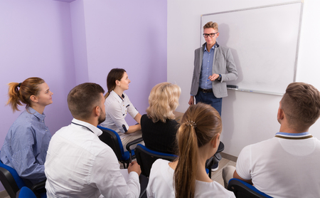 Medical male student answering near whiteboard in front group of students in auditorium