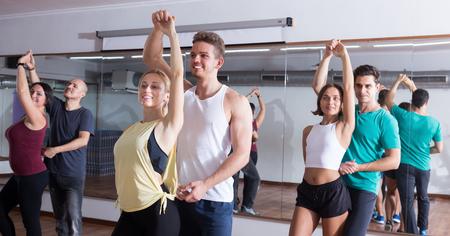 Adultos jóvenes sonrientes bailando bachata juntos en el estudio de danza