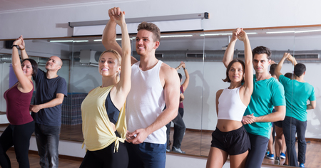 Smiling young adults dancing bachata together in dance studio