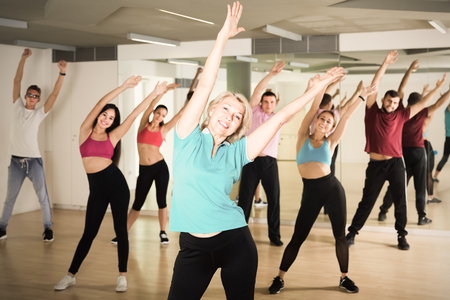 men women of different ages posing in fitness studio Stockfoto