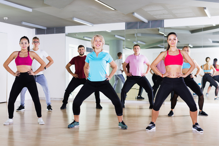 Cheerful people of different ages studying zumba dance elements in dancing class Standard-Bild
