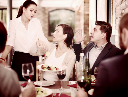 Company of people expressing dissatisfaction with the waitress about the food