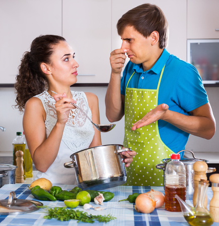 Woman with husband  preparing stinking soup at domestic kitchen