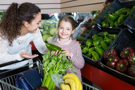 Portrait of mother and little girl buying celery together 版權商用圖片