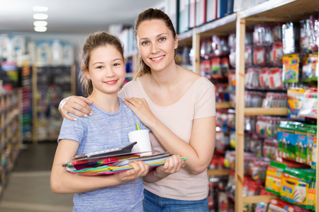 Happy positive  preteen girl with her young mother buying school supplies in stationery store