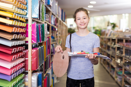 Cute tween girl holding stack of school stationery in shop, looking satisfied