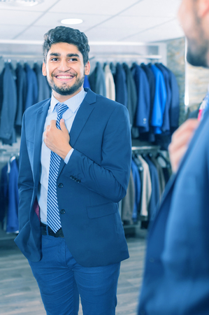 Smiling guy is trying on tie in front of the mirror in men's shop. Stock Photo