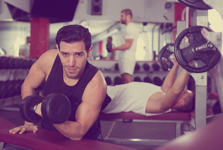 Expressive muscular young man doing exercises with dumbbells at gym Stock Photo