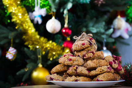 Oatmeal cookies with berries on plate on blurry background with decorated Christmas tree