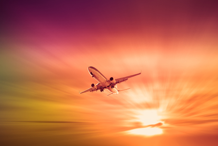Big civil passenger plane flying up in sky at sunrise time Stok Fotoğraf
