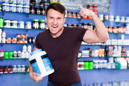 Athletic glad positive guy showing muscles while standing in store of sports nutritional supplements Stock Photo