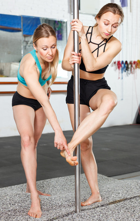 Smiling pole dance instructor helping girl on pylon in fitness club