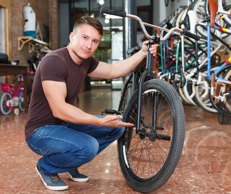 Male is shopping and choosing new bicycle in bike store. Stock fotó
