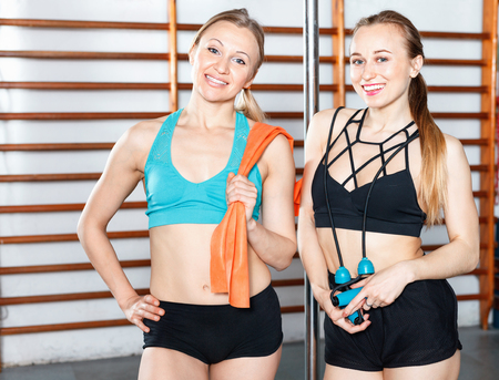 Two attractive young cheerful  smiling women taking break during workout at gym, posing together