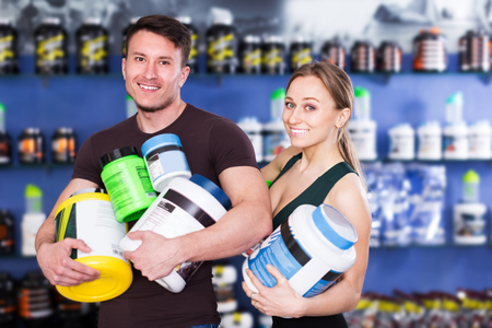 Positive physically fit people holding plastic jar of sport food supplements in shop interior