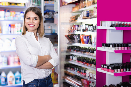 Portrait of attractive confident cheerful positive smiling salesgirl in cosmetics shop