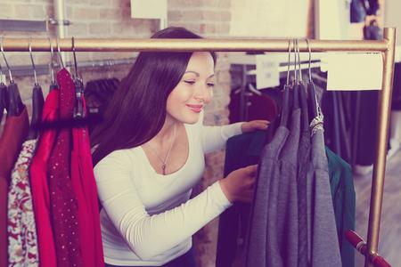 Smiling young female choosing fashion shirt  in the dress shop
