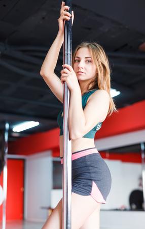 Portrait of happy female pole dancer during training in studio Banque d'images