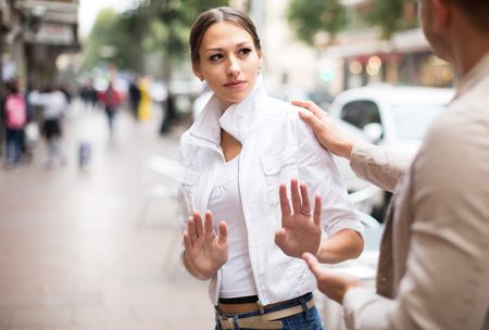 Angry woman getting rid of unwelcome stranger outdoors
