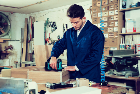 Young positive man using drilling machine to make drawer at workshop