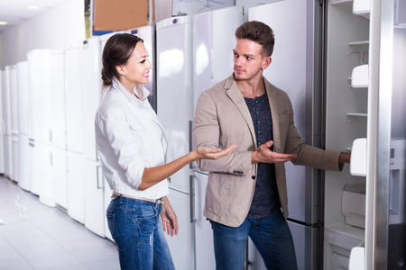 Ordinary young family selecting fridges in domestic appliances store