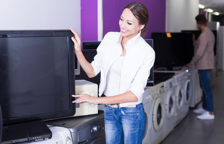 Woman  selecting TV set  in electrical goods store