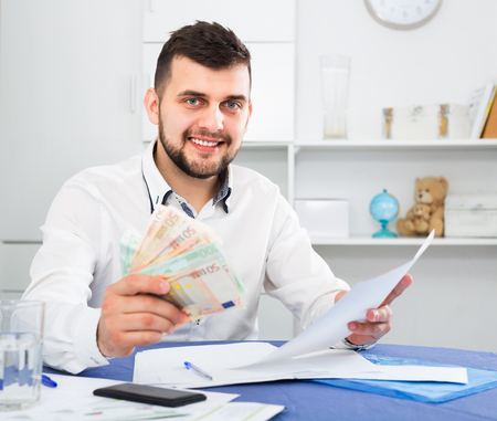 Young cheerful positive man struggling to pay utility bills and rent for his apartment
