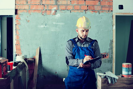 Builder man is writing report about work for client at the object.