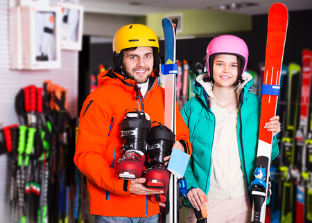 Loving young pair in skiing outfit satisfied with choice in modern shop of sports equipment Stock Photo