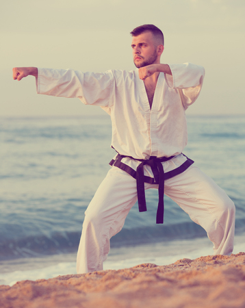 Young  male practising karate kata poses at seaside