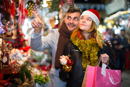 Portrait of positive young couple in hat at Christmas fair, man points to toys