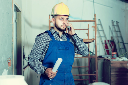 Positive designer-constructor with tools at work place Stock Photo