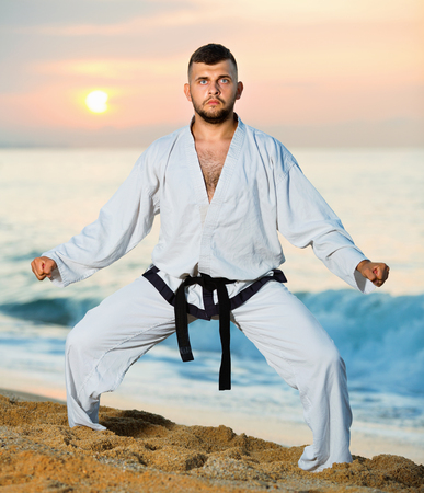 Diligent serious positive guy doing karate poses at sunset sea shore