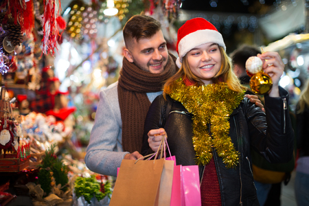 Portrait of joyful young couple in Christmas hat with Christmas toys at fair Stock Photo