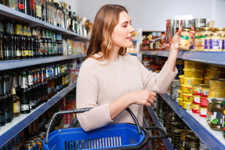 Positive glad pleasant female customer with basket holding canned goods in the food store