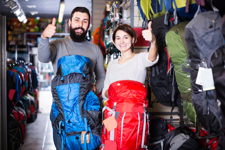 Smiling man and woman show bought backpacks for hikes in the store