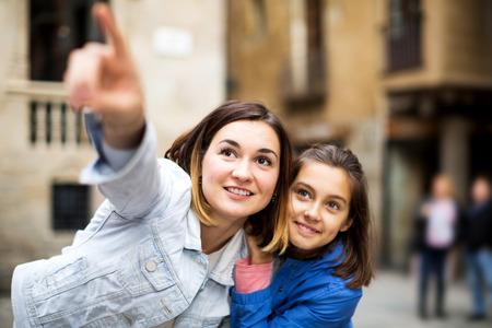 Bonita madre e hija apuntando a la vista durante la visita turística