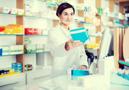 Smiling spanish female pharmacist offering assistance at counter in pharmacy Stock Photo