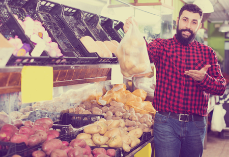 Young glad male seller offering potatoes in grocery shop
