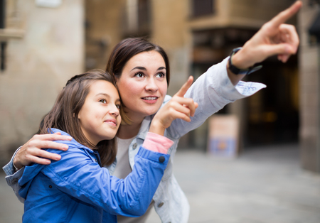Ordinary mother pointing to daughter new sight during sightseeing tour