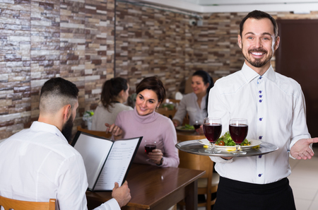 Portrait of adults guest in middle class restaurant and friendly waiter Archivio Fotografico