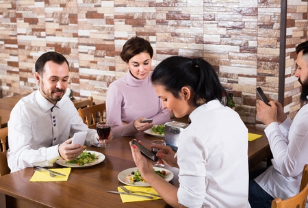 Smiling people having dinner and using smartphones at restaurant table