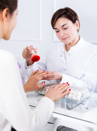 Female client doing nails in nail salon in afternoon
