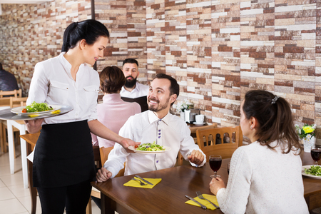 Positive waitress taking table order and smiling at tavern