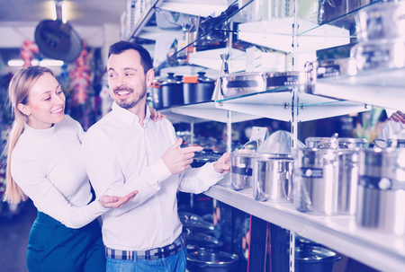 Young happy cheerful  couple choosing new saucepan in dinnerware store