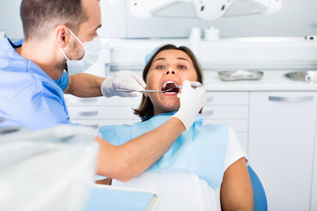 Diligent friendly dentist is treating woman patient which is sitting in dental chair in clinic.