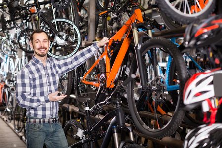 smiling spanish man in sports workshop mounts bike using special tools 写真素材